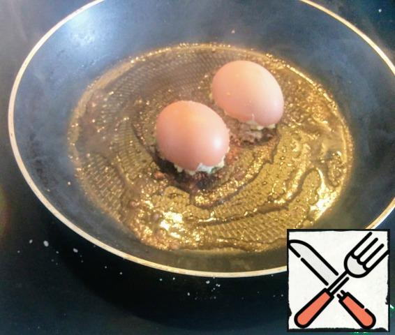 Stuff the resulting mass of the shell and sprinkle with breadcrumbs. Heat the remaining oil, put the egg halves with breadcrumbs in the pan. Cover with a lid and keep on medium heat for a few minutes.