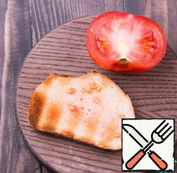 RUB the bread with garlic, once again brush well with butter and soy sauce, and then lightly soak. Cut the tomato into halves and RUB the bread well with the tomato.