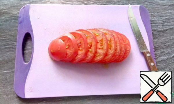 Cut the tomato into slices and place on a plate.