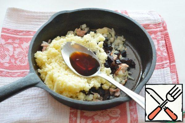 Mix the ready-made couscous, fried onions with bacon, and prunes. Add soy sauce to taste and stir.