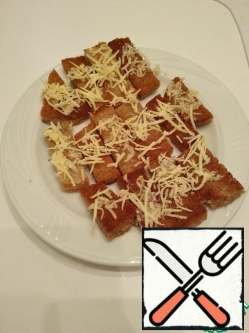 Garlic and cheese are crushed on a fine grater. Cover one side of the croutons with garlic and sprinkle cheese on top - ready))