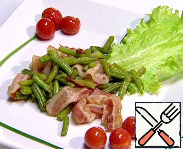 Cover the plate with a lettuce leaf, put the finished beans. Garnish the dish with fried cherry tomatoes and chives.