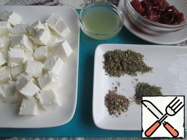 Cut the cheese into cubes. Squeeze the juice out of the lemon. Prepare the sun-dried tomatoes, Basil, thyme and pepper mixture. Dried herbs can be taken to your liking.