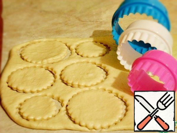 After 20 minutes, the rested dough can be cut. Roll out in a layer 7-10 mm thick, cut out different-sized circles with pastry cuts, you can use cups of different diameters.