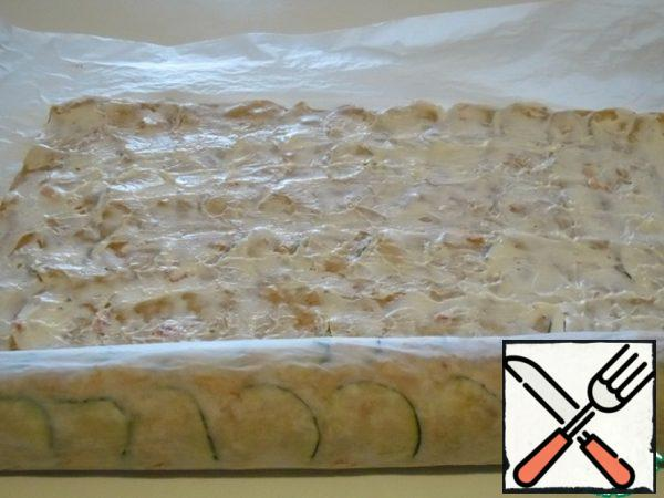 Using paper, make the first turn of the cake around the cheese, seal it and wrap it.