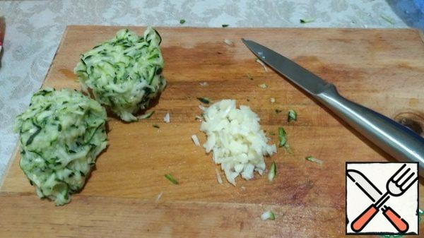 Zucchini three on a large grater. Salt, mix and leave for a few minutes. Then squeeze, pour the juice. Finely chop the garlic.