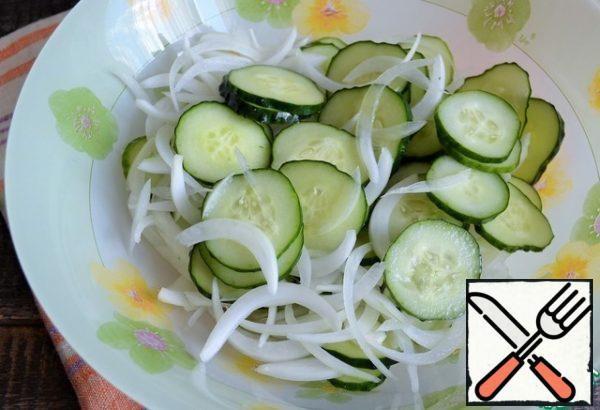 Peel the onion, cut it into feathers, and add it to the cucumbers.
