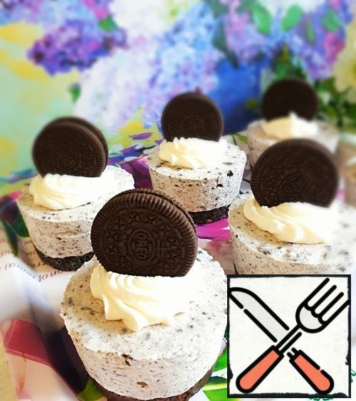 Decorate mini cheesecakes with whipped cream and whole cookies. And now pour a Cup of tea and enjoy a delicious, tender dessert!