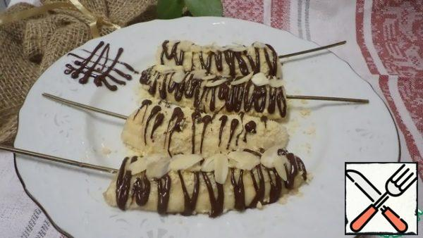 Break the chocolate, melt it in a water bath and decorate the bananas with it. Sprinkle the top with almond petals. Freeze on a silicone Mat or plastic wrap, turn over, smear with honey and sprinkle with cookie crumbs, decorate to your taste and transfer to a plate! Bon appetit!
