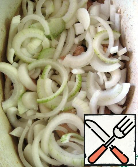 Cut the onion into half rings and put it on top of the chicken pieces in a mold.