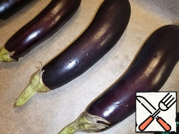 Heat the oven to 200°C. Cover the baking sheet with parchment. Arrange the washed eggplants. Make a few small punctures. And send in the oven until ready, it takes me 10-15 minutes. Focus on your oven.