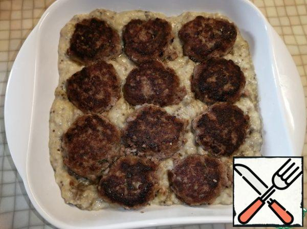 Put the eggplant puree in the baking dish and lay out the meatballs.