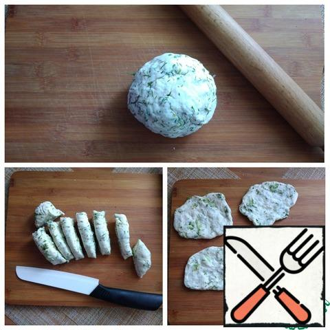 """Continue to knead the dough with the addition of herbs. Roll the """"sausage"""" with a diameter of about 5-6 cm and divide it into 8 equal parts. It is necessary to form not thick tortillas from each part. I will shape it with my fingers, about 0.5 cm thick. I have a frying pan with a diameter of 24 cm and I want to put 4 pieces of tortillas on it. You can roll out the tortillas with a rolling pin, then the surface will have to be dusted with flour."""