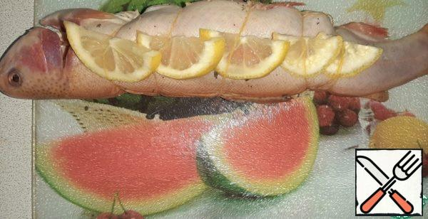 Cut the lemon. Tie the trout with a thread, put lemon slices on the sides under the thread.