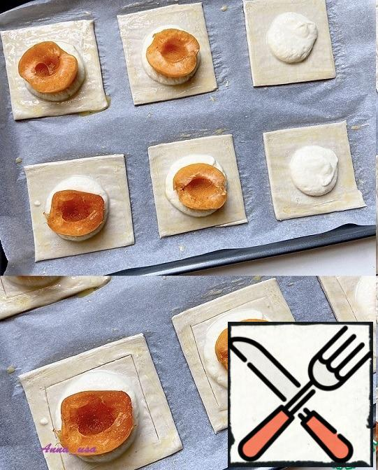 Put a tablespoon of ricotta in the middle of each square and half an apricot on top. Draw a square around the filling with a little pressure on the knife, do not cut the dough. Bake in a preheated oven (205*C or 400*F) for 15-20 minutes until Golden brown.