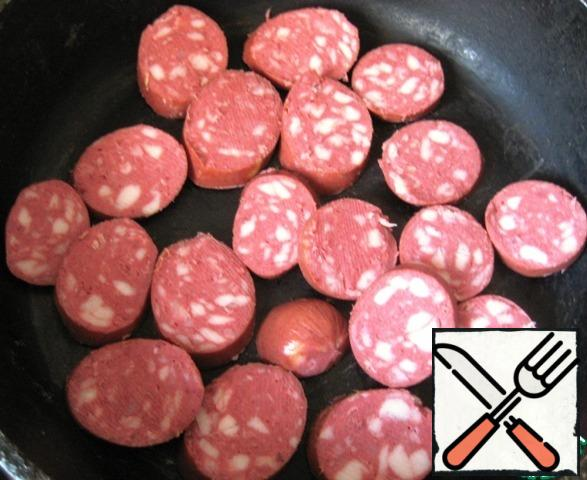 Heat the vegetable oil in a frying pan and fry the sliced sausages.