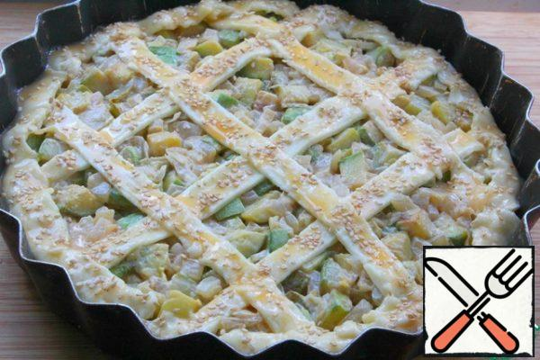 Spread the zucchini layer on top. Make strips from the remaining dough. Make a pie. Brush with egg yolk and sprinkle with sesame seeds if desired.