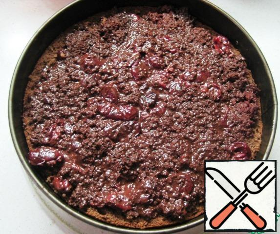 Putting together a cake: fill the sponge cake blank with chocolate cherry filling, level the top.