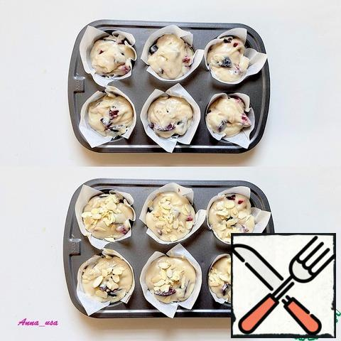 Fill the molds for muffins and sprinkle with almond petals (optional, on request). You can grease the molds with butter and flour, or use paper cups for baking muffins and cupcakes. I used parchment. Cut into squares and put in molds.