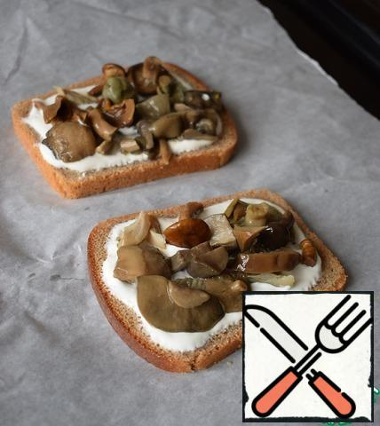Put the mushrooms on the bread greased with sour cream.