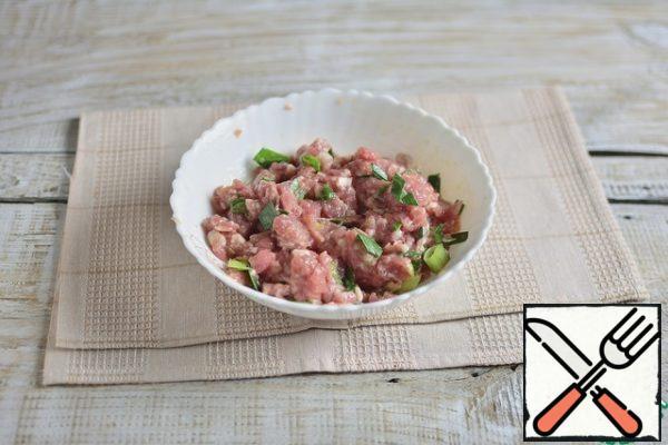 In the minced meat, add garlic through a press, chopped green onions, salt to taste, stir.