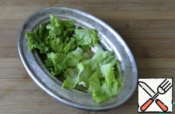 We take a salad bowl for serving, tear the washed, dried lettuce leaves into it.