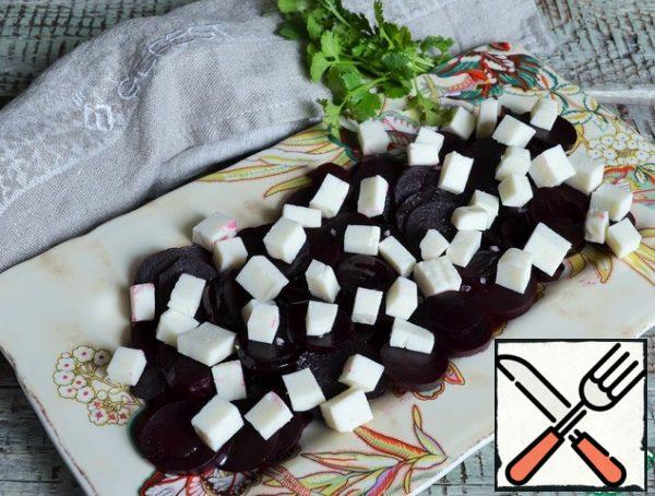 Cut the cheese and put it on the beetroot.