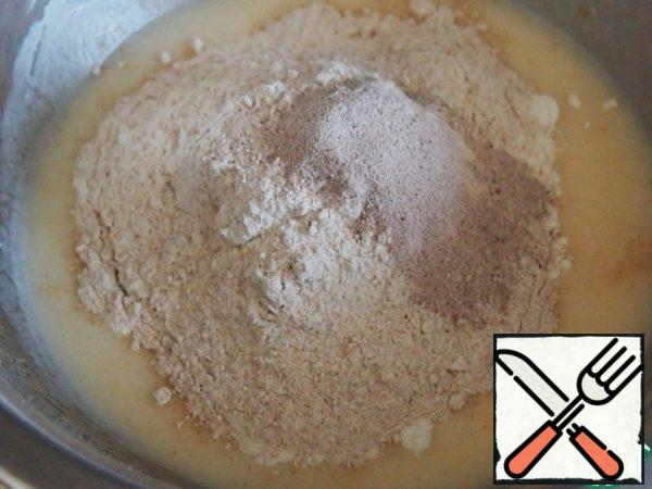 Add both types of flour and baking powder and stir. I have baking powder for gingerbread, so it's dark. You can use, of course, only white flour, but still the presence of a little wholemeal flour in baking greatly improves the taste of the dough, and for Apple baking it is just perfect.
