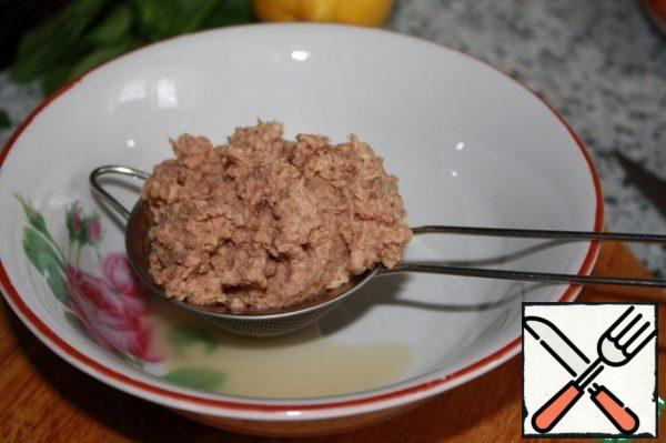 Drain the excess liquid from the tuna can.