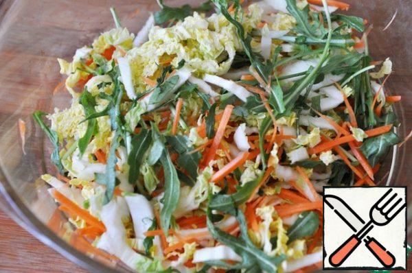 Add arugula to the cabbage and carrots, you can add any salad mix and herbs as desired.