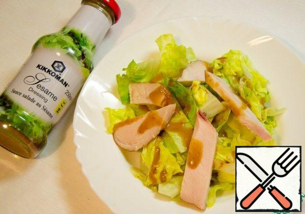 Large slices of chicken casually cover the salad.
