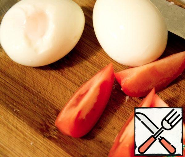 Cut the eggs and tomatoes into half-moons and put them on plates.
