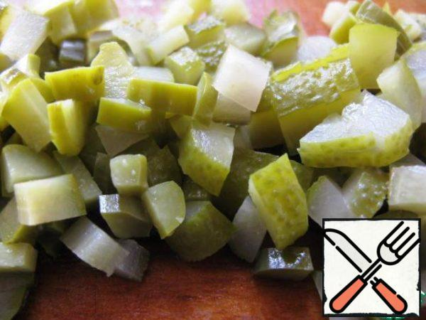 Chop olives, capers and pickled cucumbers.