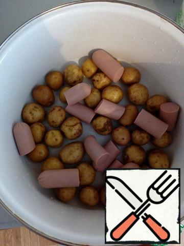 Wash potatoes, cut the sausages, put everything in a baking dish.