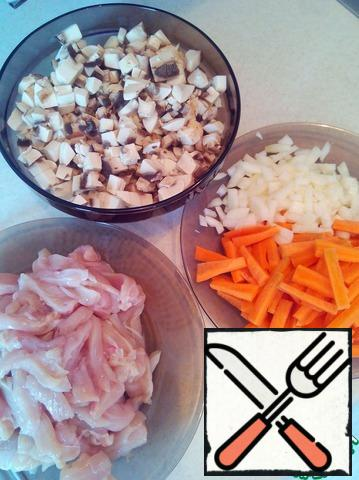 Cut chicken fillet into thin strips, carrots into cubes, onions and mushrooms.