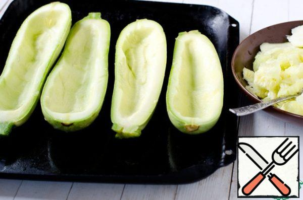 Cut the zucchini in half lengthwise. Remove part of the pulp from each half with a spoon, leaving the sides. Put the pulp aside, it will go into the filling.