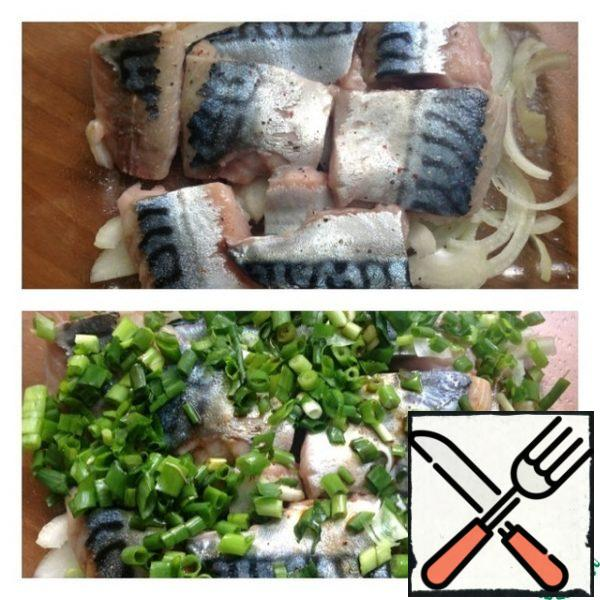 Cut the mackerel into fillets and cut into small pieces. Grease the baking dish with vegetable oil and put the onion cut into thin half rings on the bottom. Put the fish on top. Sprinkle with lemon juice, salt and pepper. Finely chop the green onions and put them on the fish, season with soy sauce on top.