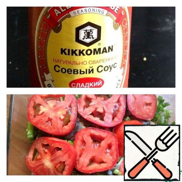 Cut the tomatoes into thin slices and put them on the green onions. Put the fish in the oven at 190 g for 15 minutes.