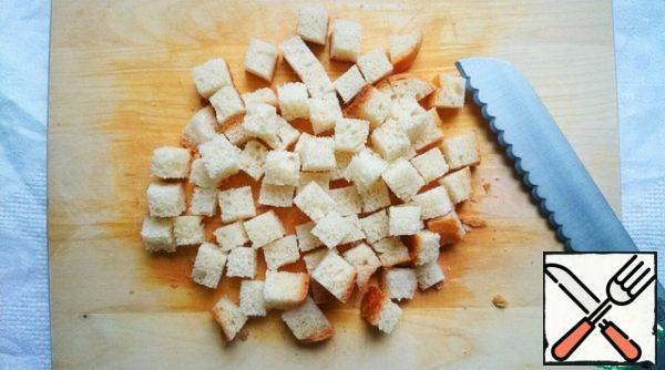Bread is cut into cubes, the thickness can be any, but the smaller the cubes, the faster the crackers will be ready.