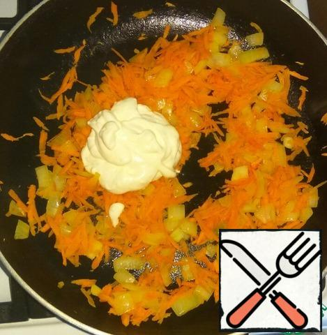 Onion cut into small pieces, carrots grate on a large grater. Fry the onion in vegetable oil until transparent, add the carrots. Fry for a couple of minutes. Add sour cream or mayonnaise, mix and warm well.