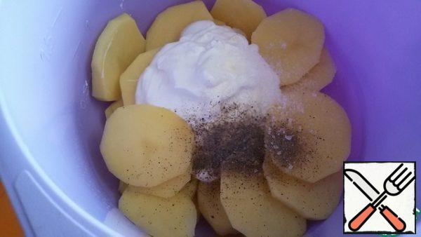 Peel the potatoes and cut them into 5-6 mm thick slices. Add 2 tbsp sour cream, salt and black pepper.