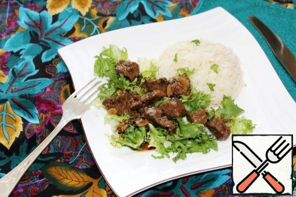 We put salad leaves on plates, meat on top, and boiled rice as a side dish.