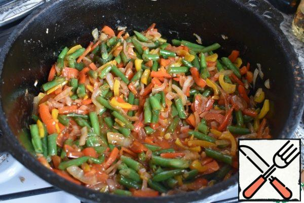In the pan where the meatballs were fried, put the onion cut into half rings. Fry for 5 minutes, then put the chopped bell pepper and fry for another 2-3 minutes, then the string beans and continue to fry for 2-3 minutes.