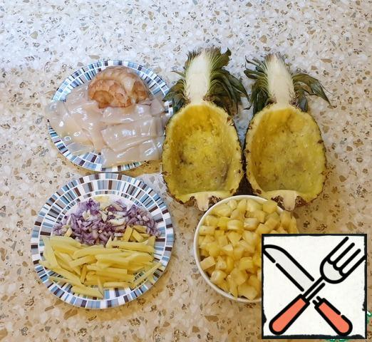 Boil the rice. Chop the onion, garlic, and ginger. Cut the pineapple in half. Remove and slice the pineapple pulp.