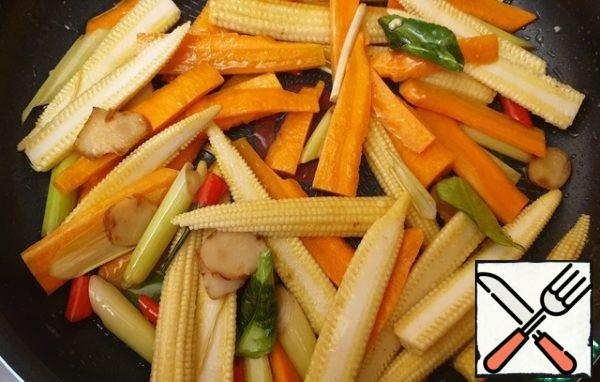 Cut the corn in half and the carrots into strips. Fry the carrots for a couple of minutes, add the corn. Fry for a couple of minutes.