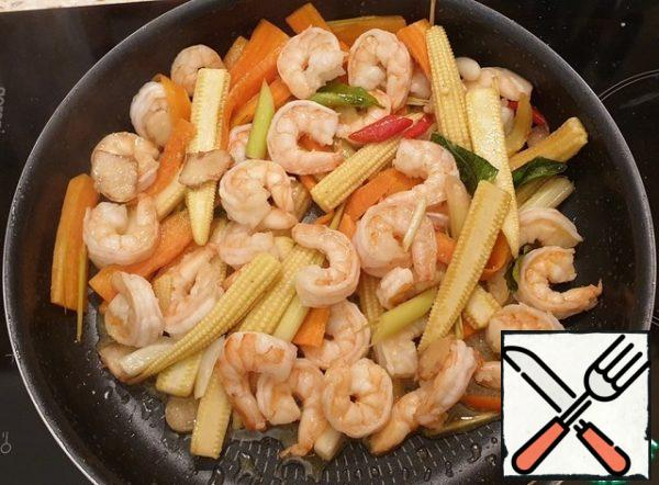 Add the shrimp and garlic. Salt. Fry the prawns for a couple of minutes on each side (the prawns should turn pink, but do not overdo it). You can serve it with Thai sweet chili sauce.