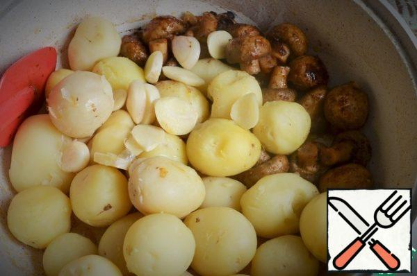 Heat the oil, fry the onion feathers, add the mushrooms. Fry for 5-8 minutes, medium heat, stirring. Then add the potatoes and garlic petals.