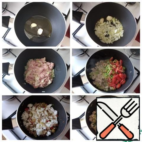 Making the filling. Heat the oil in a saucepan, spread the garlic and hold it in the oil for a minute so that it gives its flavor to it. I have a large clove and I cut it in half. Garlic can be removed. Spread very finely chopped onion, gild it. Next - minced meat. Fry it a little and add the vegetables finely chopped: zucchini; pepper slices; cherry; olives. Fry until the liquid evaporates. Sprinkle with salt and pepper to taste. Spread the finished rice, mix and sprinkle with finely chopped parsley. The filling is ready.