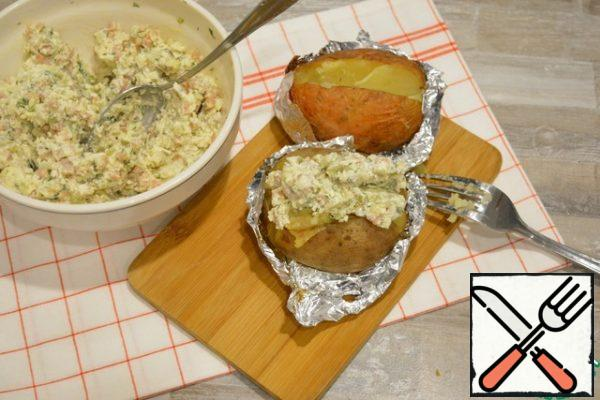 Cut the finished potatoes with a knife. Use a fork to gently mash the pulp and put a good portion of the filling inside.It is very tasty to mix the filling with the hot pulp, so that the cheese is slightly melted, and the garlic reveals its flavor.