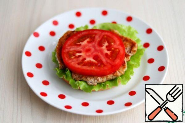 Cut the hamburger bun into two parts. On the lower part, put a lettuce leaf, then fried Turkey breast fillet, then grease the fillet with the prepared avocado and garlic cream, then a plastic tomato, then a lettuce leaf again.